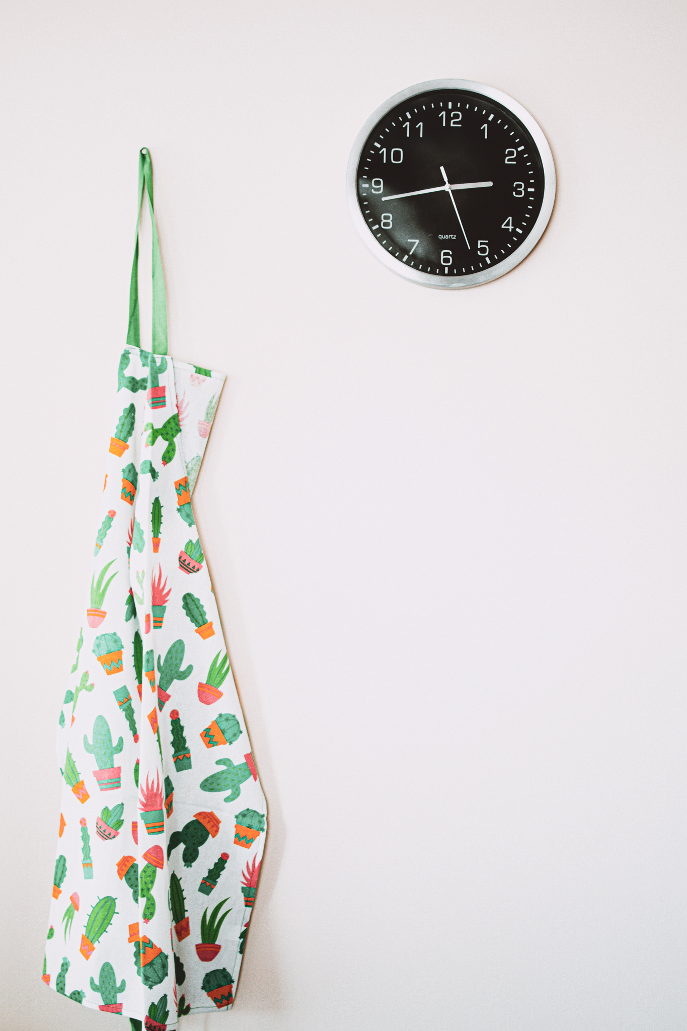 white-and-green-cactus-pattern-apron-near-clock